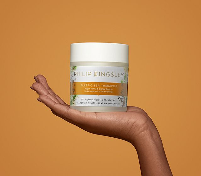 A hand holding a tub of the Philip Kingsley Therapies hair mask scented with mayan vanilla & orange blossom.